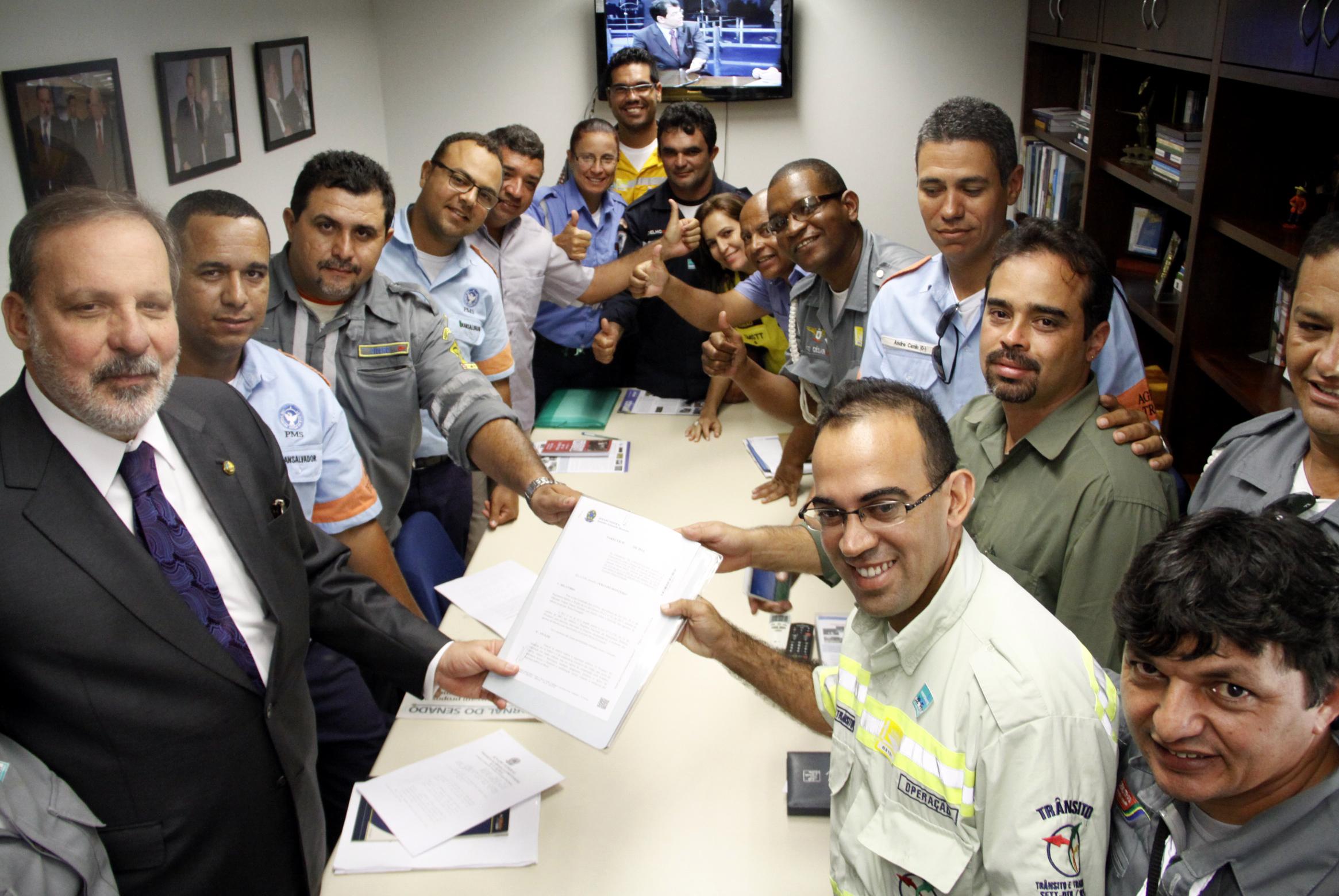 Armando entrega projeto ao presidente do Sindicato dos Agentes de Trânsito de Pernambuco, Jair Fidélis, ao lado de guardas municipais.