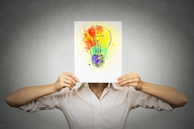 woman with colorful lightbulb covering face